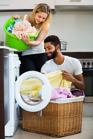 Man and woman loading laundry into front loading washing machine