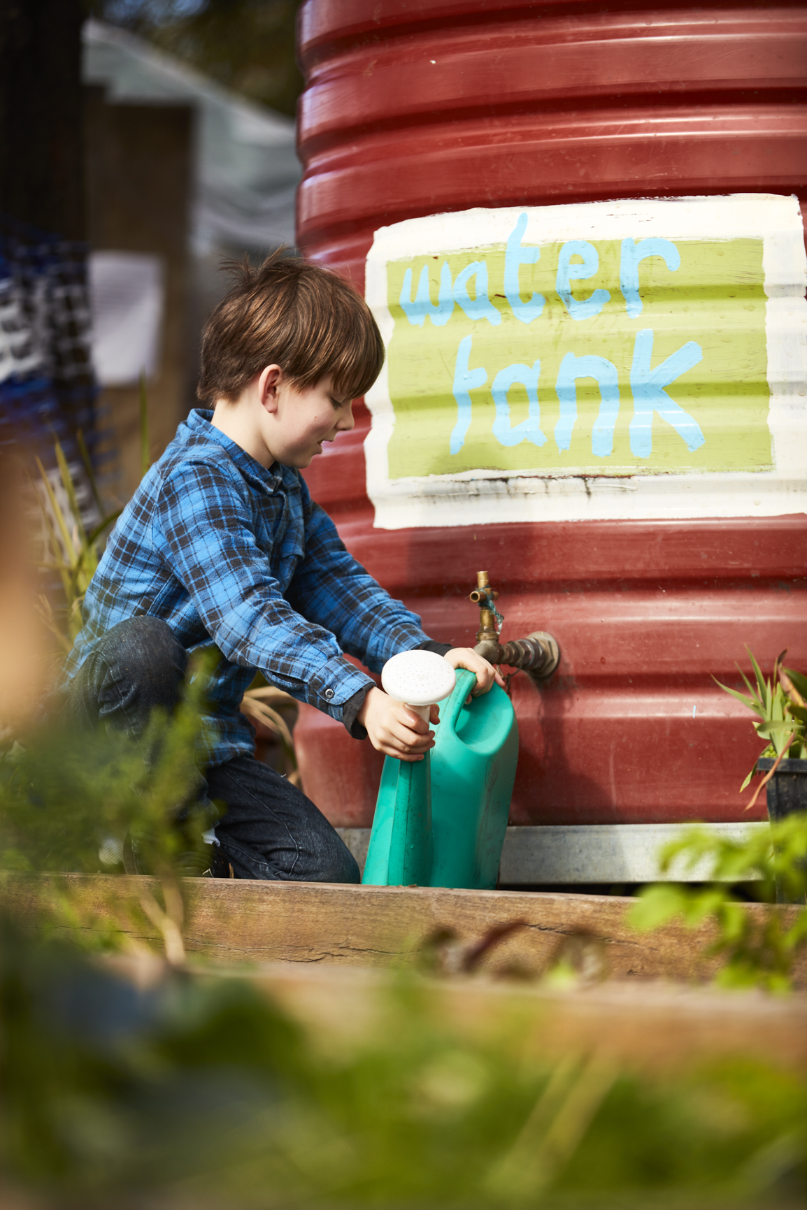 Young child getting water from a tank to fill his watering bucket