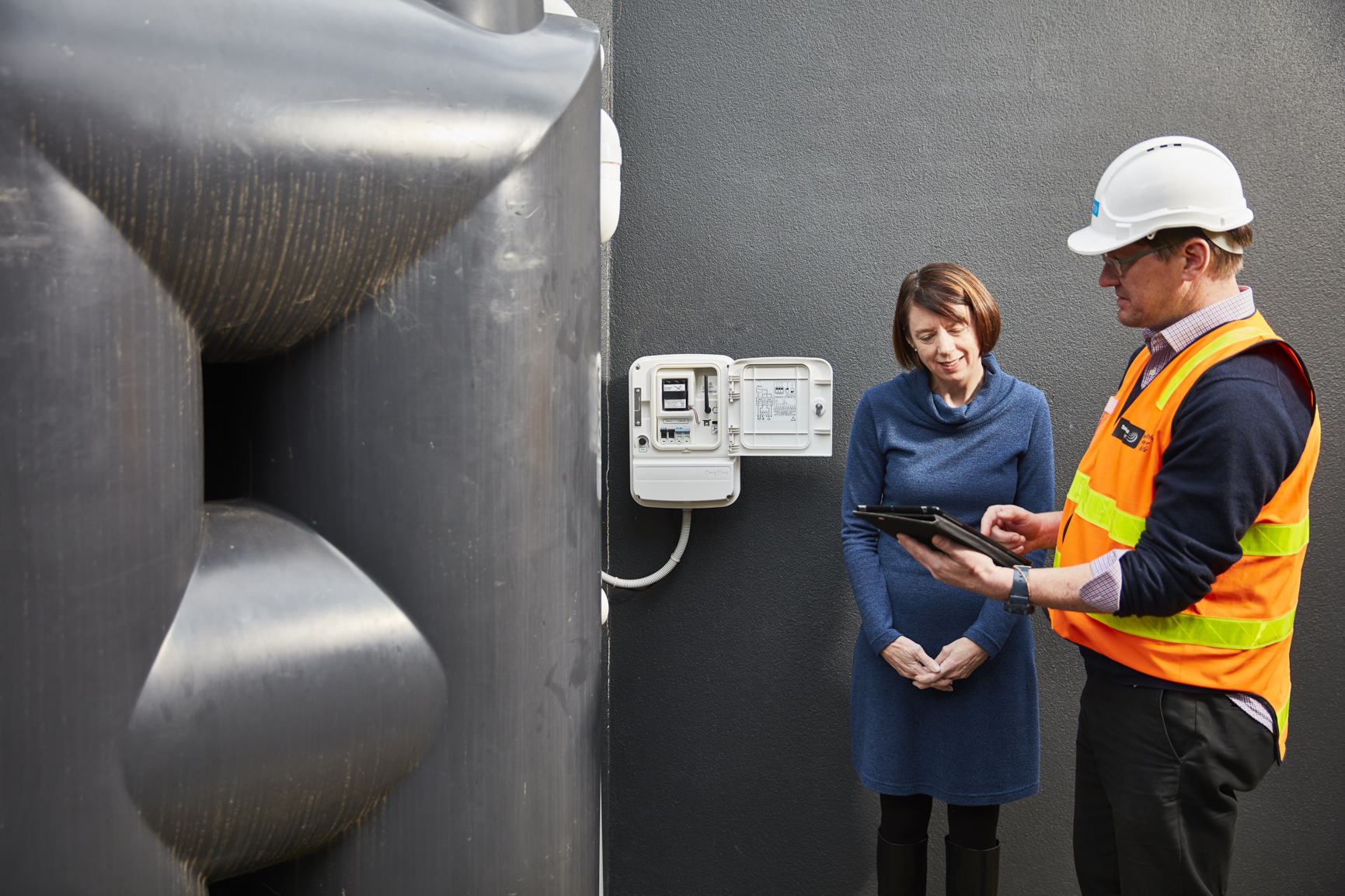 Man and woman standing next to a water meter, looking at an iPad