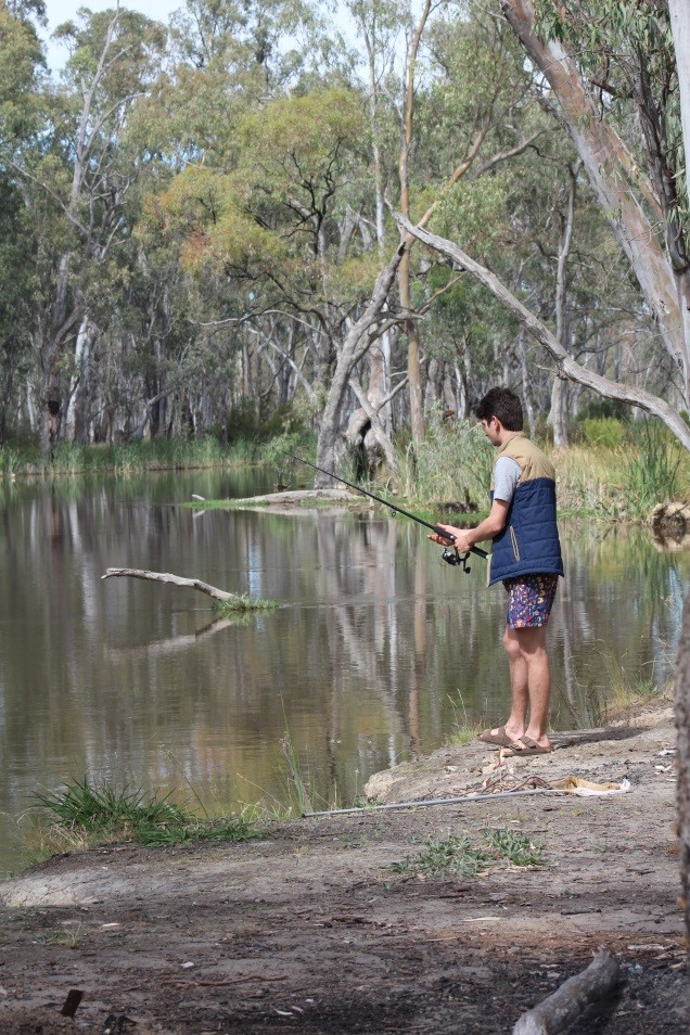 Man standing on bank of river, fishing with a fishing rod