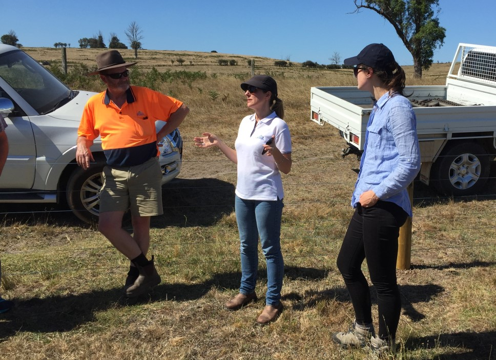 Landholders stand in front of a fence with utility trucks behind them