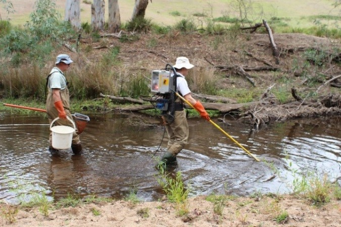 two men in waders carrying monitoring equipment in a stream