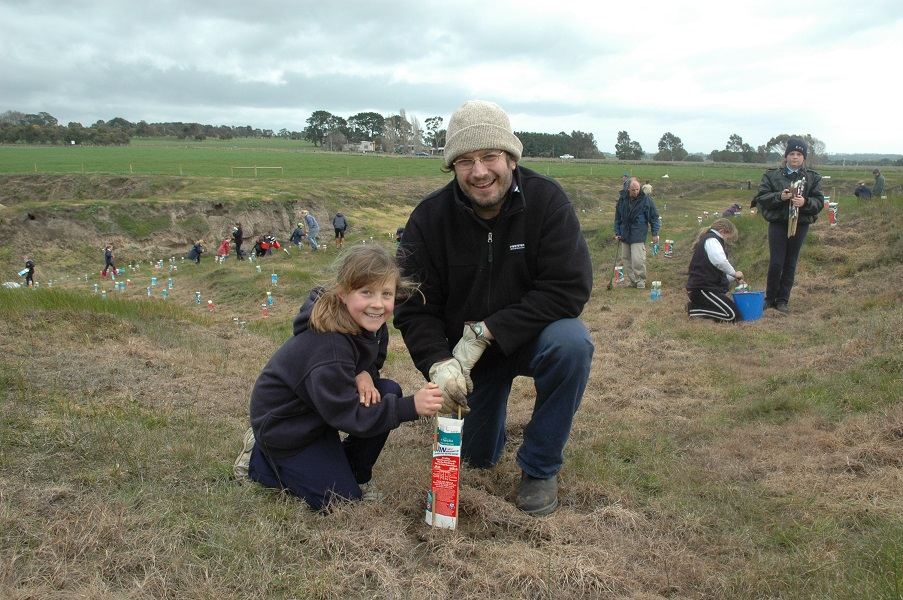 Teacher and child planting trees, more volunteers and students in background