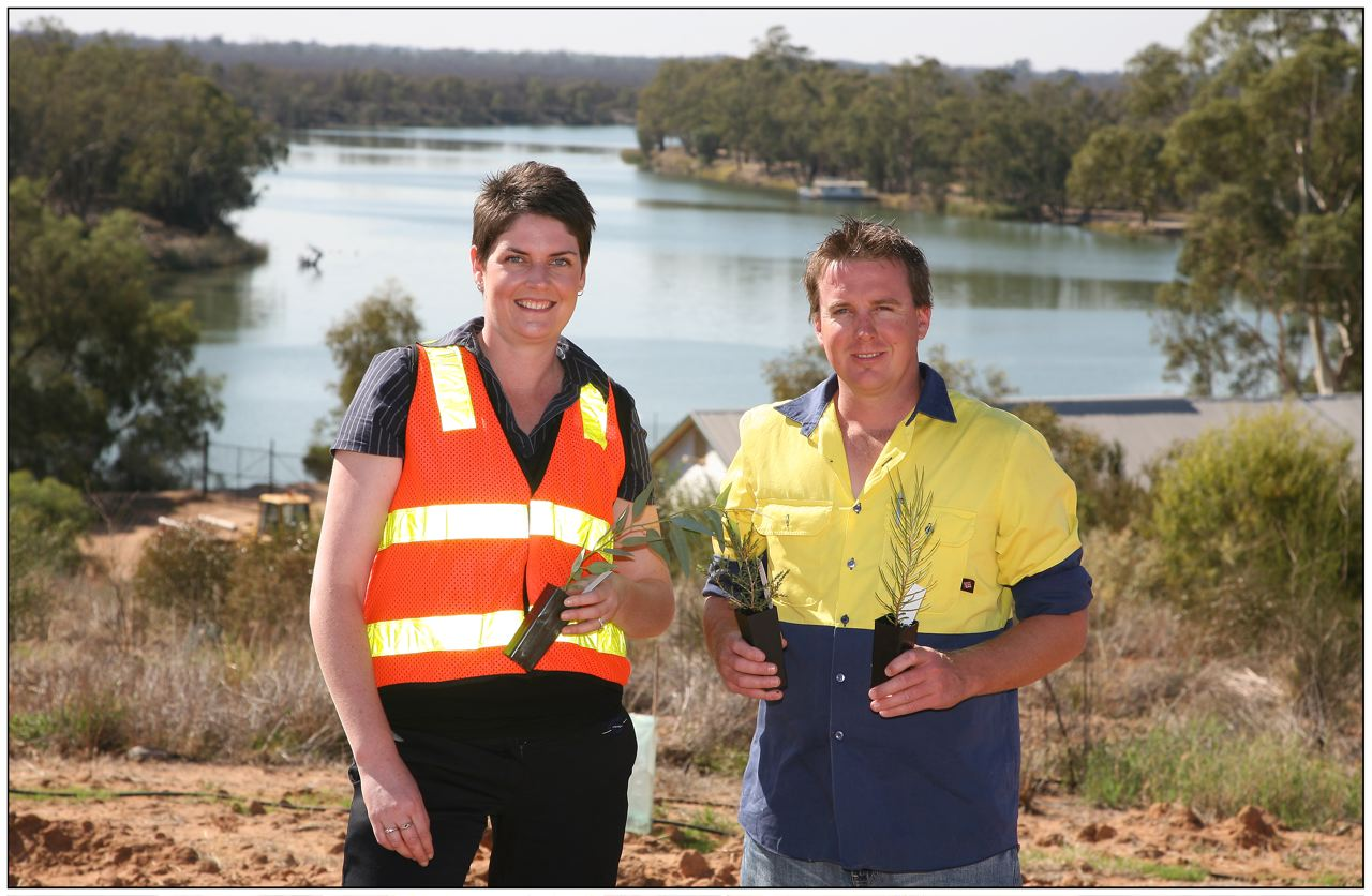 A woman and a man wearing hi-viz holding plants ready for planting