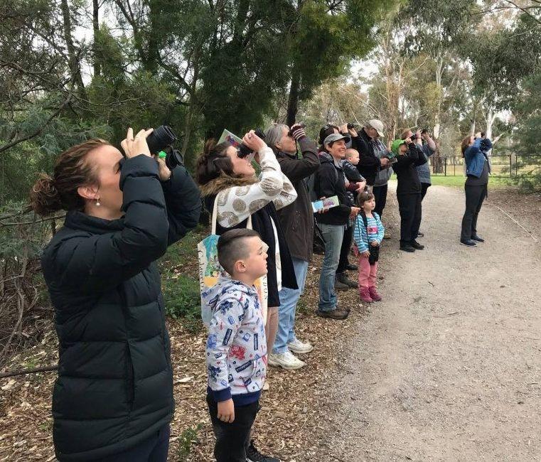 Teachers and students birdwatching through binoculars