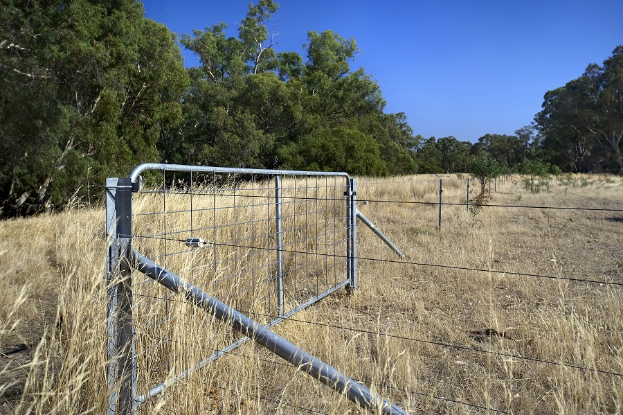 Fenced land with gate in foreground