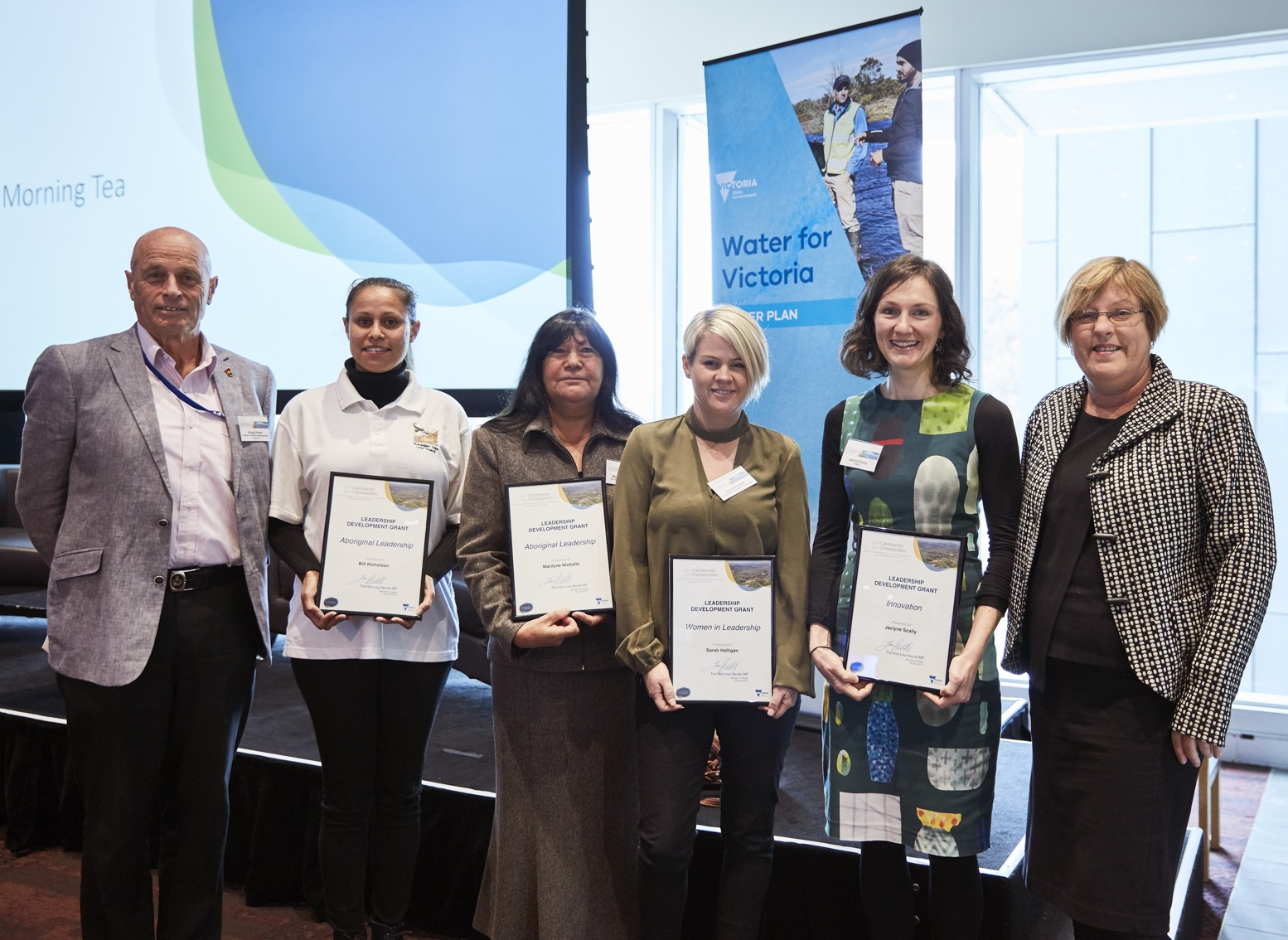 Minister for Water, Lisa Neville standing with the Chair of the Victorian Catchment Management Council, Angus Hume congratulate the 2017 OCOC grant recipients: (L-R) Tarlina Gardiner accepting on behalf of Bill Nicholson, Marilyne Nicholls, Sarah Halligan and Jaclyne Scally.