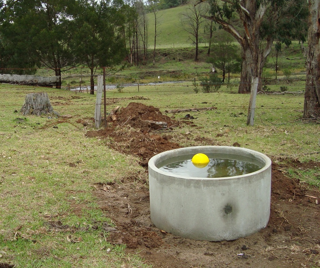 Trough for watering stock in foreground, fence in middle ground, stream in background