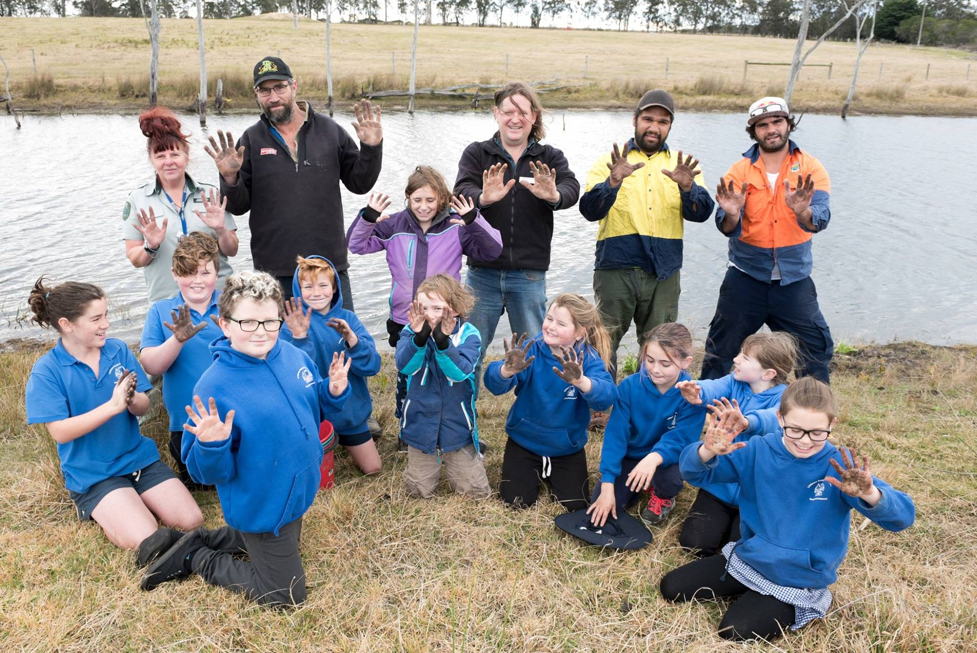 Students from Lindenow Primary School, Gunaikurnai Land and Water Aboriginal Corporation and Greening Australia show off their dirty hands after planting trees at Skull Creek
