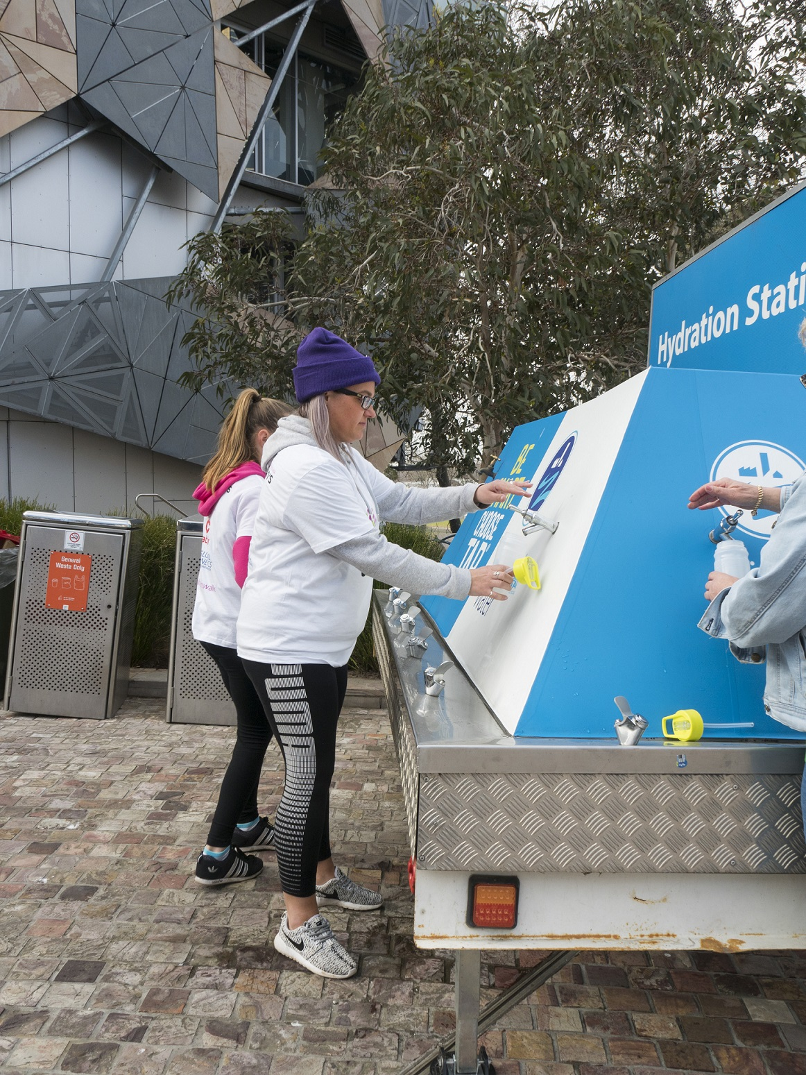 Photo of two ladies refilling thier water bottle with tap water from a water bubbler trailer.