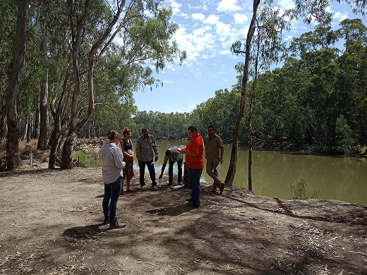 Traditional owners and staff standing in a clearing by a river.